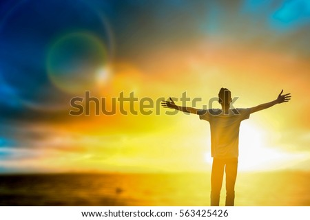Silhouette male thought positive rise hand on the beach background. Christian praise God on thanksgiving day man standing up for wellbeing open arms over nature sun concept victory spirit wisdom