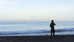 Silhouette man cleaning up the beach with sea and nice blue sky background