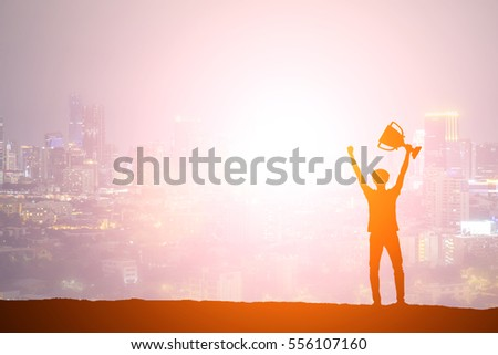 Silhouette man holding up a gold trophy cup as a winner in a competition #556107160