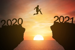 silhouette man jump from the mountain from 2020 to 2021 years with the sunset or sunrise background. Happy and success growth with new year 2021 concept
