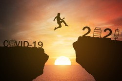 silhouette man jump from the mountain from 2020 which covid-19 spread to 2021 years which hope to found vaccine of corona virus with the sunset ,sunrise background. Happy health new year 2021 concept