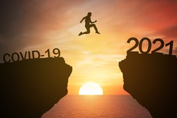 silhouette man jump from the mountain from 2020 which covid-19 spread to 2021 years with the sunset or sunrise background. Happy and success growth with new year 2021 concept