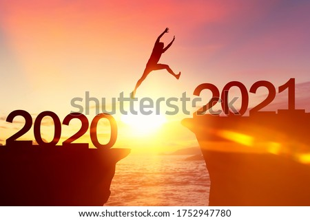 Silhouette man jumping between cliff with number 2020 to 2021 at tropical sunset beach. Freedom challenge and travel adventure holiday concept. Vintage tone filter effect color style.