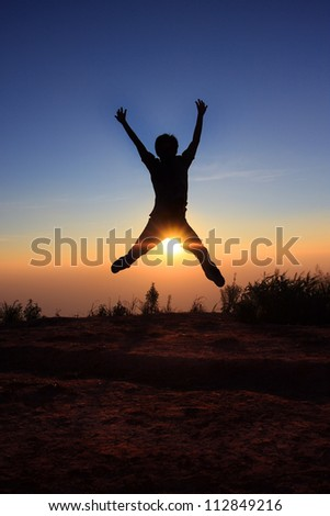 Silhouette man  jumping over the sun