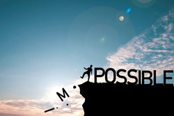 Silhouette man kicking alphabet from cliff to change impossible to possible with cloud blue sky , Positive mindset concept.