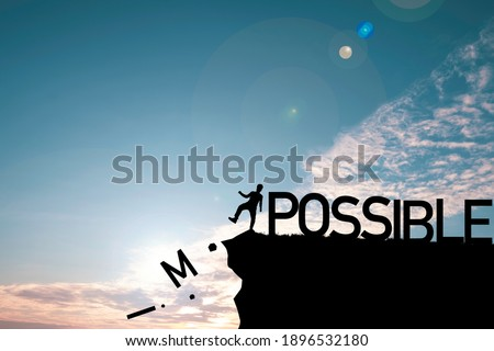 Silhouette man kicking alphabet from cliff to change impossible to possible with cloud blue sky , Positive mindset concept. Stock fotó ©