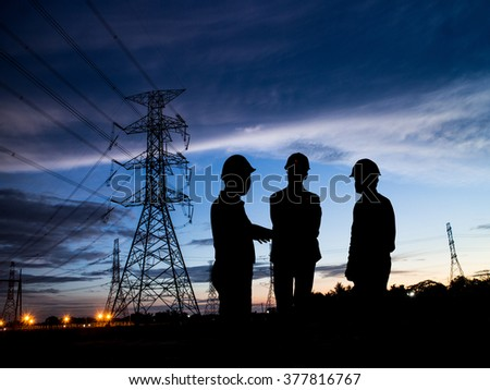 silhouette man of engineers standing at electricity station over Blurred electricity power