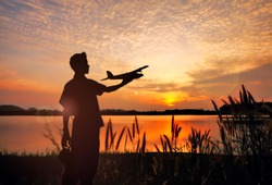 silhouette man play RC Airplane when the sunset.