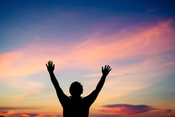 Silhouette man praying and worship to GOD on the sunset sky.Man praying to GOD in the morning.Young man hand praying,Raised Hands in prayer.Concept for faith,Praise the lord spirituality and religion.