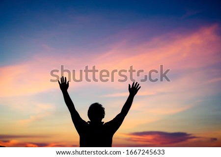 Silhouette man praying and worship to GOD on the sunset sky.Man praying to GOD in the morning.Young man hand praying,Raised Hands in prayer.Concept for faith,Praise the lord spirituality and religion. Stockfoto ©