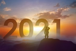 Silhouette man standing on peak of mountain and looking to gold sunset with 2021 year background.  Success plan, Business goal and strategy and new year concept.
