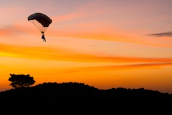 Silhouette man under control  parachute come down to the beach at sunset time with sun set sky background.