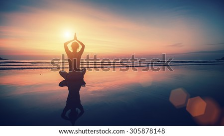 Silhouette meditation girl on the background of the sea and sunset. Yoga and healthy lifestyle.