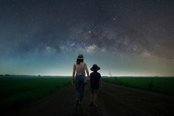 Silhouette, mother and child couple Walking on the road, holding hands together Outdoor nature On the night of the stars and the Milky Way happily. Long exposure, with grain.