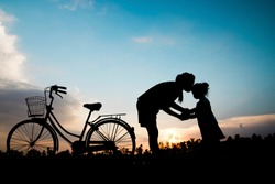 silhouette mother kiss daughther with bicycle in sunshie, happy family and signle mom concept