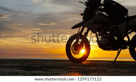 Silhouette motorcycle with helmet and bag against sunset background. #1299173122