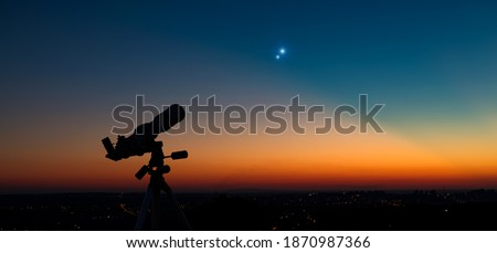 Photo of  Silhouette of a astronomy telescope with twilight sky.