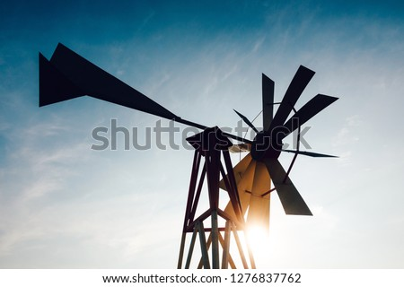 Silhouette of a backlit steel windpump at sunset, sun and sky in the background