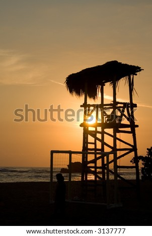 Silhouette of a beach lifeguard tower during sunset