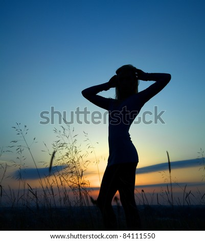 Silhouette of a beautiful girl over sunset
