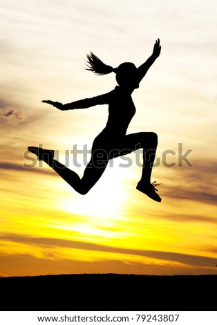 Silhouette of a beautiful jumping woman against yellow sky with clouds at sunset