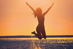 Silhouette of a beautiful, slim girl who jumps on a background of a sunset on the beach.