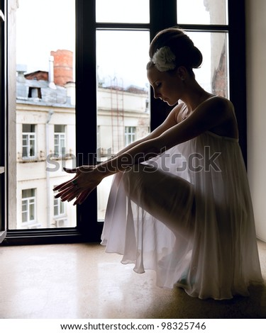 Silhouette of a beautiful thoughtful bride sitting on window sill