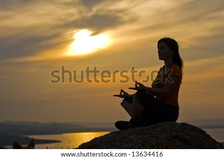 Silhouette of a beautiful woman meditating on a rock at the sunset