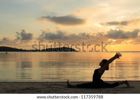 Silhouette of a beautiful yoga girl at sunrise on the beach,,Hanumanasana,Monkey Pose