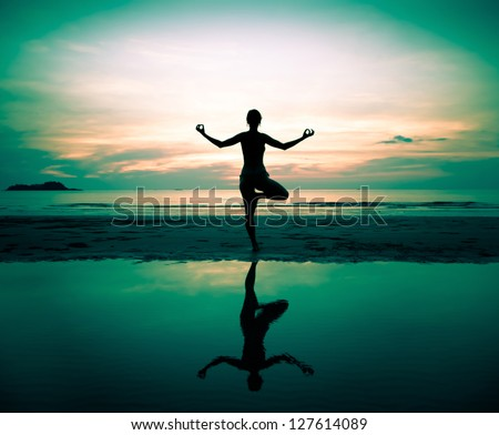 Silhouette of a beautiful yoga woman at sunset (in surreal colors)