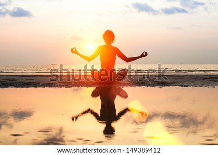 Silhouette of a beautiful yoga woman on the beach at sunset