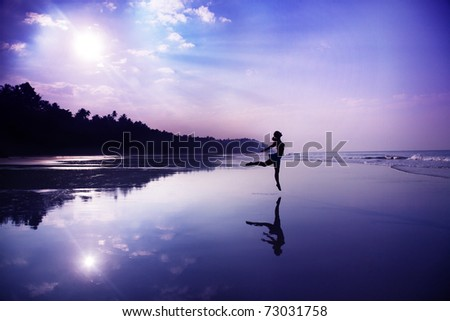 Silhouette of a beautiful young girl dancing on the beach at the sunrise in purple colors