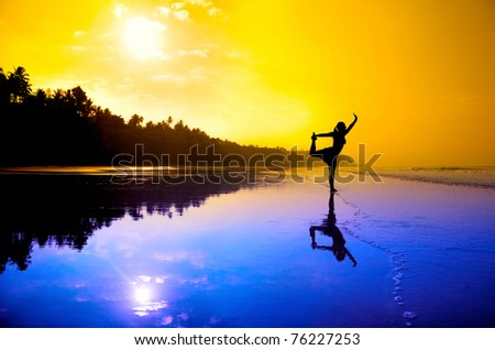 Silhouette of a beautiful young girl doing yoga natarajasana dancer pose on the beach at the sunset in purple and orange colors