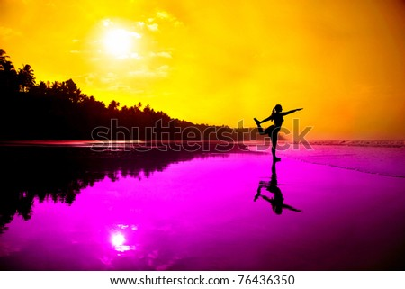 Silhouette of a beautiful young girl doing yoga natarajasana dancer pose on the beach at the sunset in magenta and orange colors