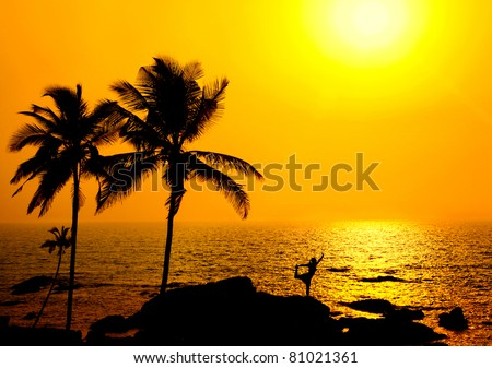 Silhouette of a beautiful young girl doing yoga natarajasana dancer pose on the beach at the sunset in orange colors and palms around in India, Goa, Vagator beach