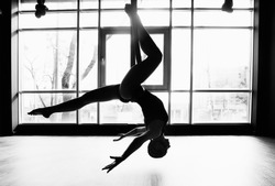 Silhouette of a beautiful young woman doing fly yoga and stretches in the gym.