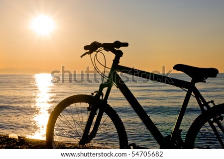 silhouette of a bike on the beach at sunset - stock photo