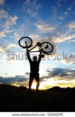 Silhouette of a biker holding his bicycle