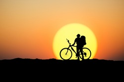 Silhouette of a biker on the mountain top. Sport and active life concept