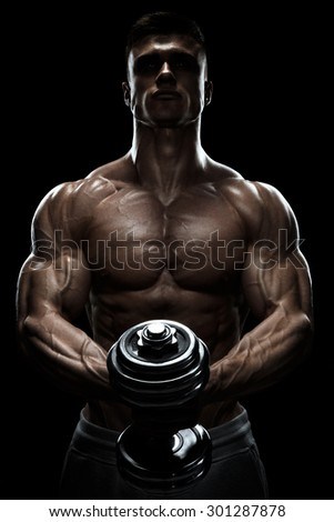 Silhouette of a bodybuilder. Power athletic man pumping up muscles with dumbbell. Confident young fitness man with core muscles, power hands and clenched fists. Dramatic light.