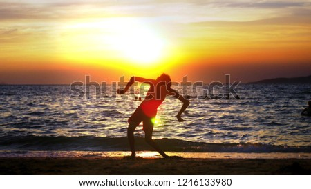 silhouette of a boy on the background of the sea sunset, funny teenager boy dancing on the background of a sunset on the sea