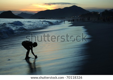 Silhouette of a boy playing at the beach at sunset