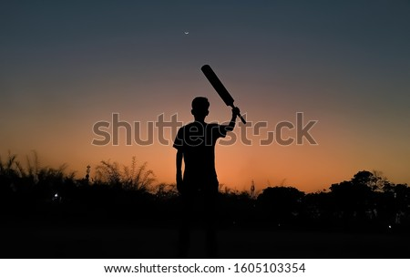 Silhouette of a boy playing cricket in the evening with the crescent moon in the beautiful sky full of variety of colors after sunset as wallpaper background. Gully cricket. Cricket wallpaper. India.
