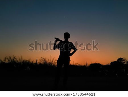 Silhouette of a boy playing cricket in the evening with the crescent moon in the colorful sky after sunset as wallpaper background. Gully cricket. Cricket wallpaper. India. Cricket during pandemic.