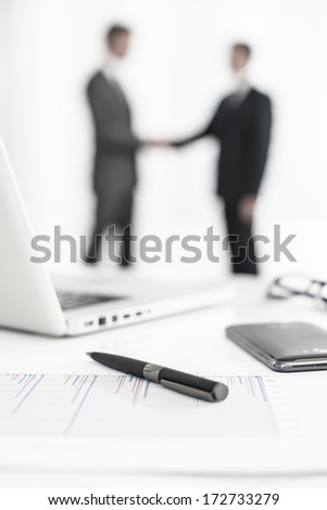 silhouette of a business people  with symbolic business objects in the foreground