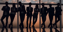 silhouette of a business team standing next to the office window