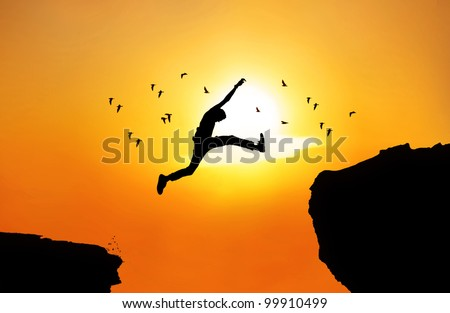Silhouette of a businessman jumping a wide cliff. Shot outdoor at sunrise