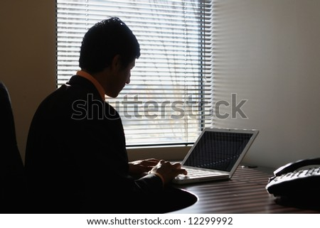 Silhouette of a businessman sitting on a laptop by a window