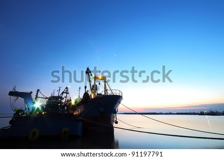 Silhouette of a cargo ship tanker during blue hour immediately after sunset