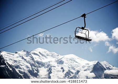 Silhouette of a chairlift in Mont Blanc Massif, in the background is Mont Blanc peak, Alps, Chamonix, France #418811473